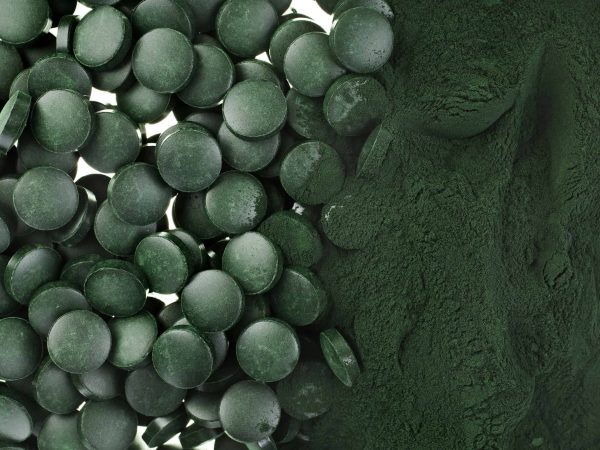 29370380 – spirulina powder and tablets algae nutritional supplement heap surface close up top view, background