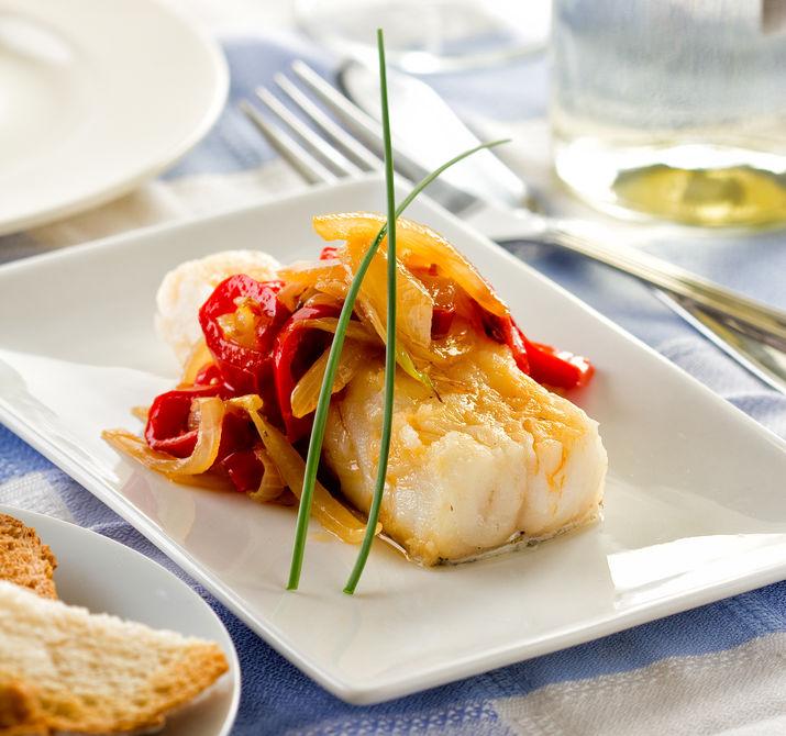 Bacalao o merluzzo servito con cipolla e aglio peperone.