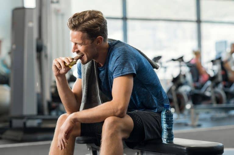 Uomo che mangia una barretta proteica in palestra