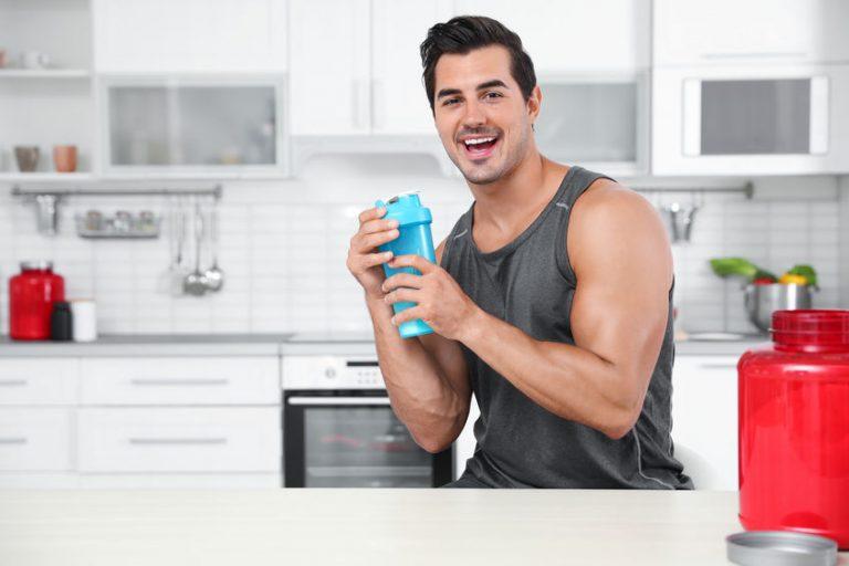 Uomo sorridente con shaker in mano
