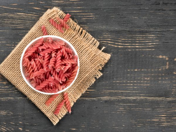 Red uncooked pasta fusilli in a bowl on wooden background
