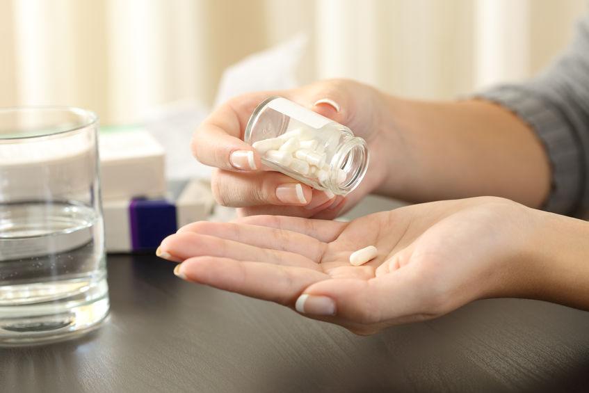 Donna che prende una pillola dalla bottiglia