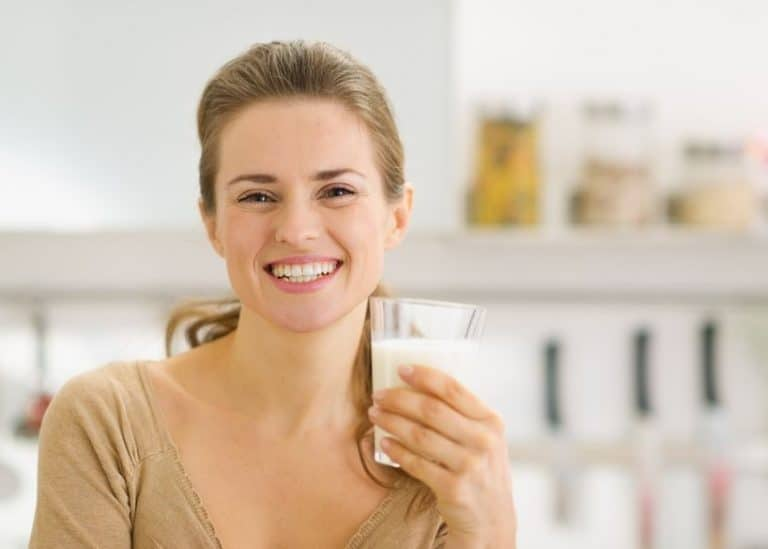 Donna che sorride con bicchiere in mano