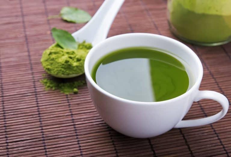 Tazza di tè verde e cucchiaino di polvere di tè verde