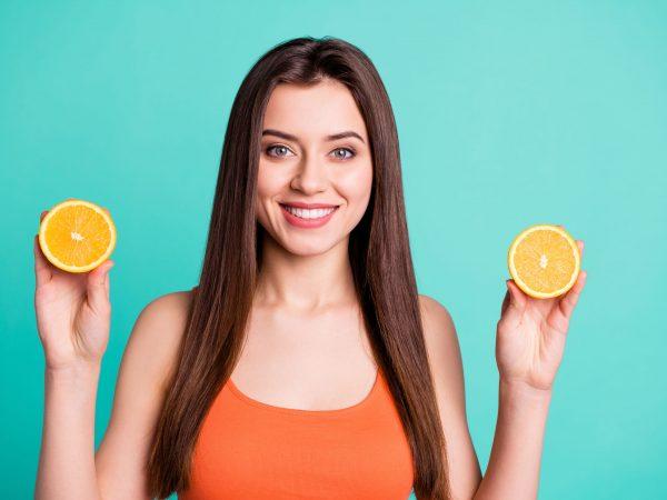 Donna che tiene le fette di arancia