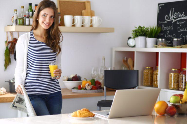 Donna in cucina con un bicchiere di succo d'arancia in mano sul portatile al tavolo