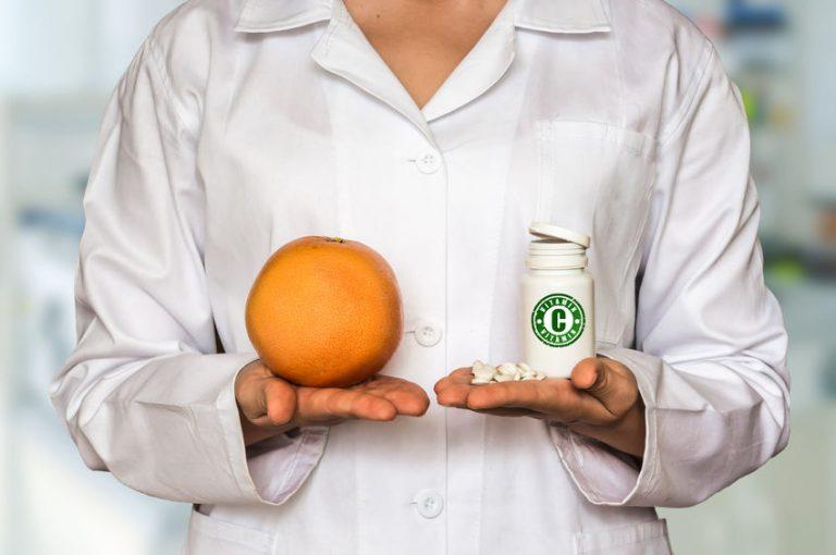 dottoressa con un'arancia nella mano destra e una bottiglia di vitamina C nella mano sinistra