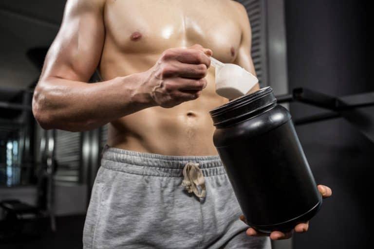 Uomo muscoloso che mescola un integratore