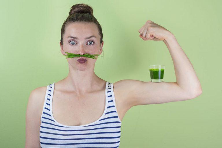 Donna che indica la forza con il wheatgrass sul braccio