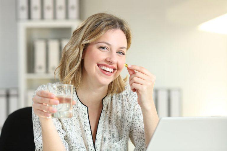 Donna che sorride mentre assume un integratore