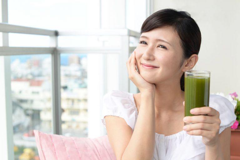 Donna che sorride sorreggendo un frullato verde