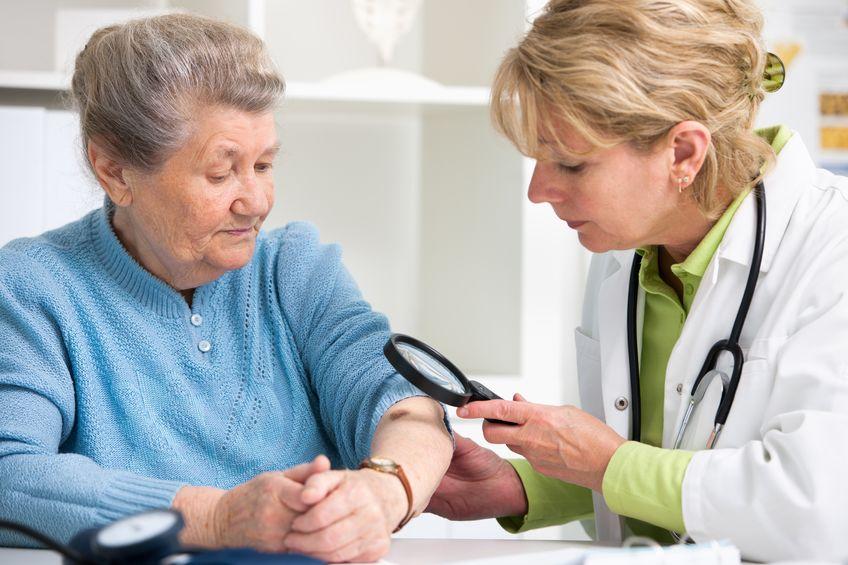 Donna che ispeziona un braccio di un'anziana