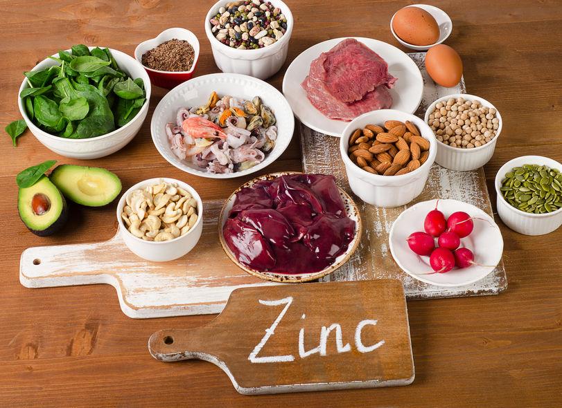 Alimenti con minerale di zinco su un tavolo di legno.