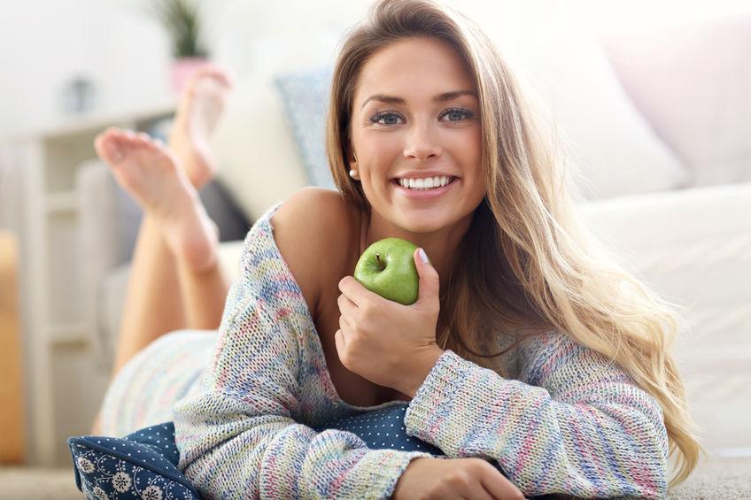 Donna che sorride con una mela in mano