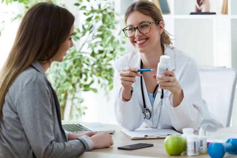 Dottoressa che mostra un integratore a una paziente