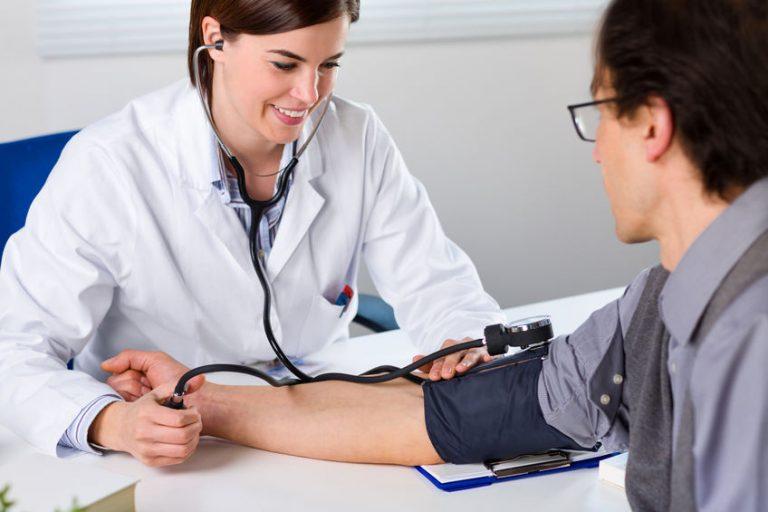 Dottoressa che misura la pressione