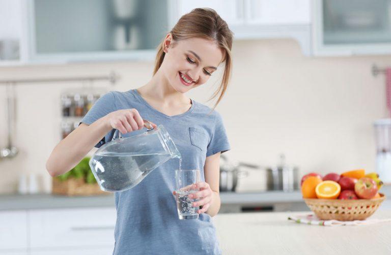 Donna sorridente che si versa da bere