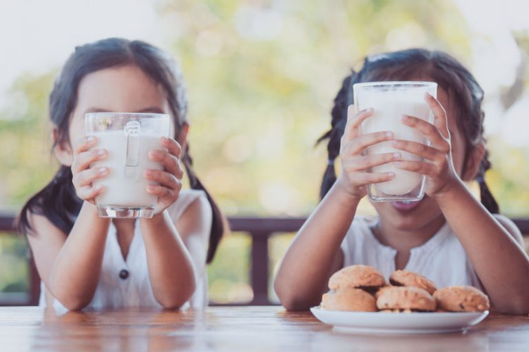 Bambine con bicchiere di latte in mano