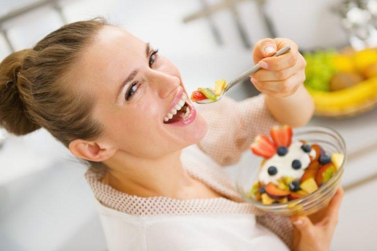 Donna che sorride mangiando