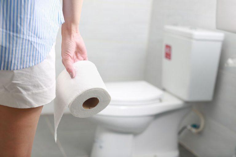 Donna con rotolo di carta igienica mentre si avvicina al WC