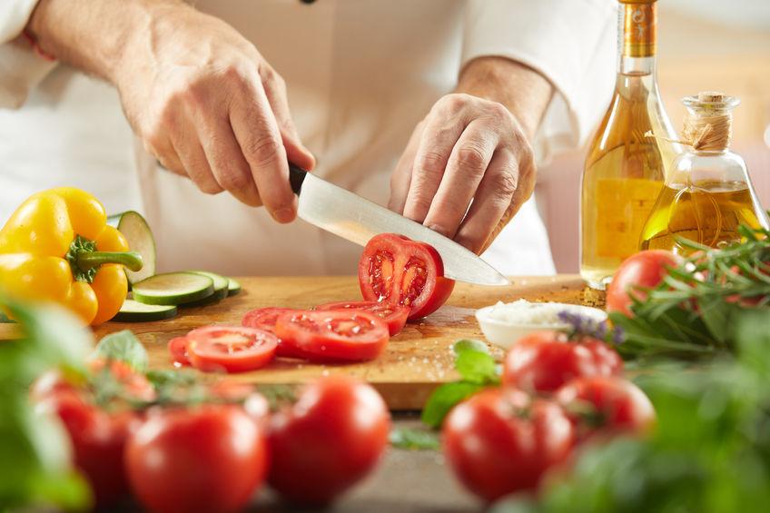 Chef che affetta i pomodori