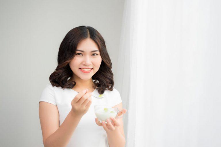 Donna che sorride mangiando uno yogurt