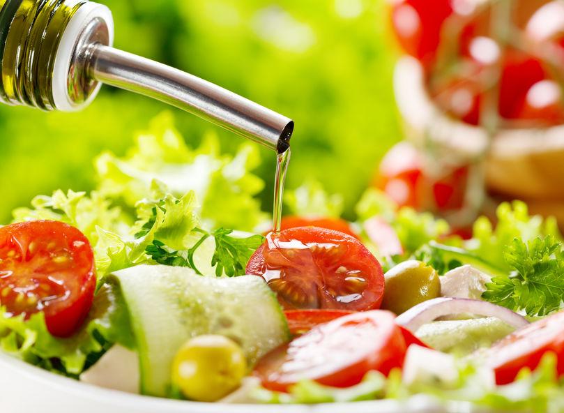 Olio versato su insalata di verdure