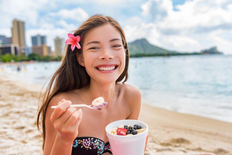 Donna sorridente mangiando frutta