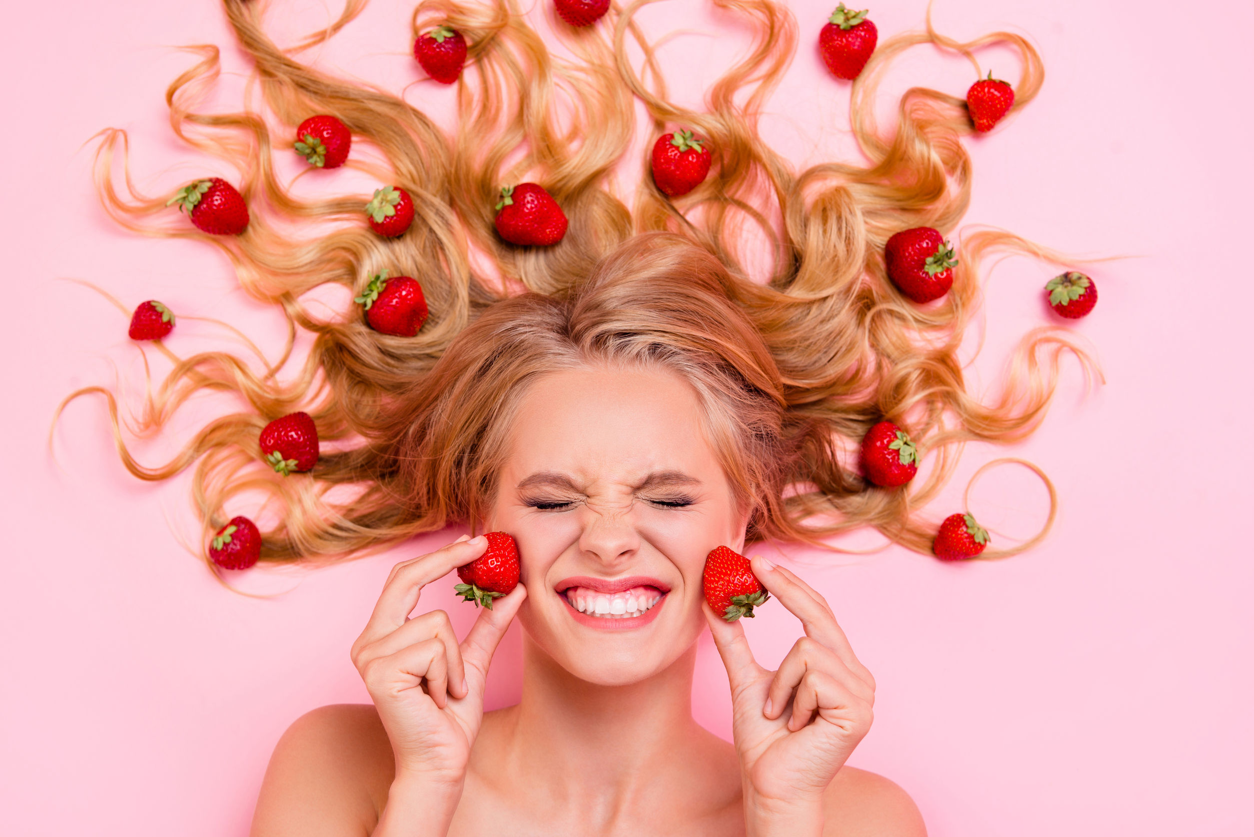 Donna con fragole sul viso e capelli