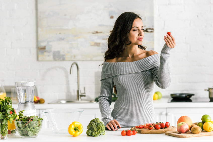 Donna in cucina che guarda un pomodoro