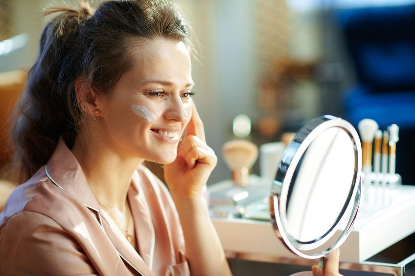Donna che sorride allo specchio mettendosi la crema
