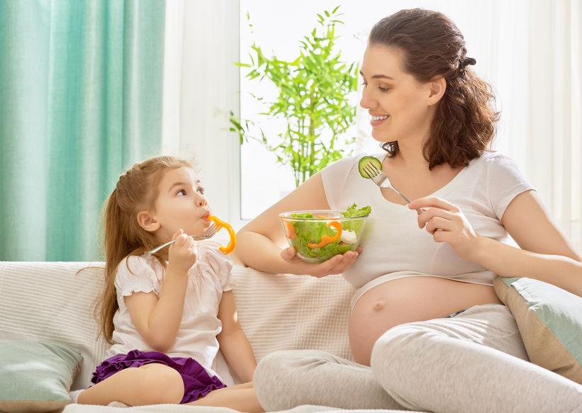 Donna incinta che mangia sano insieme a una bambina