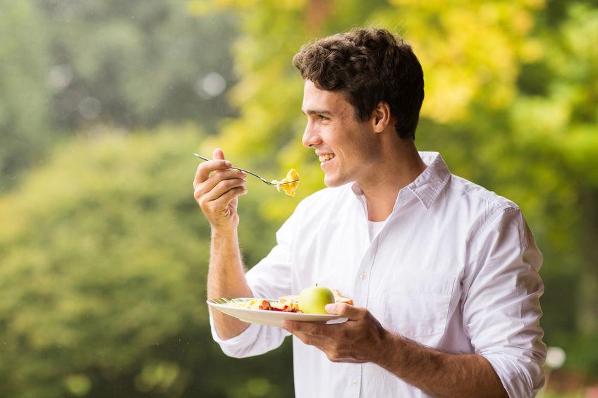 Uomo che mangia all'aria aperta