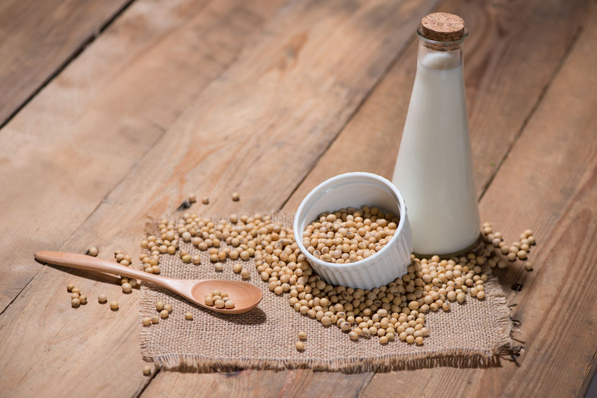 Soy milk or soya milk and soy beans in spoon on wooden table.