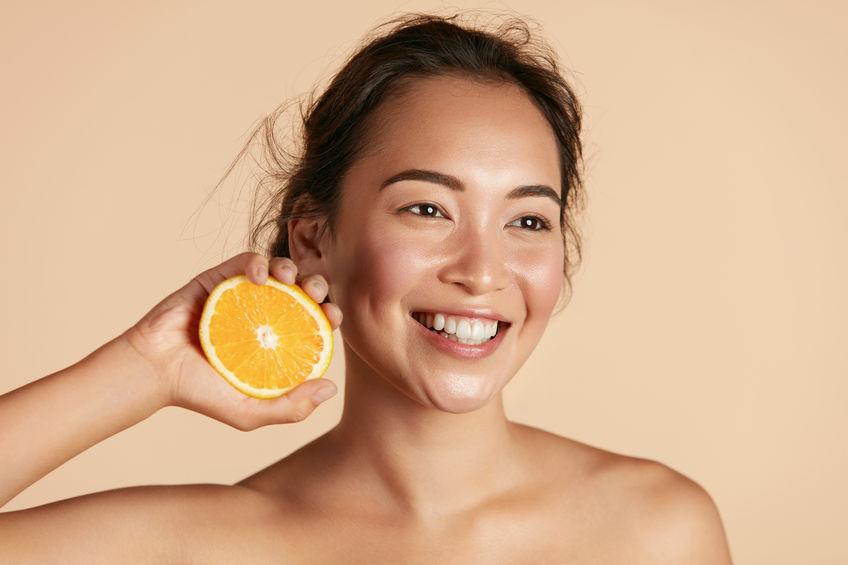 Donna sorridente con mezza arancia in mano