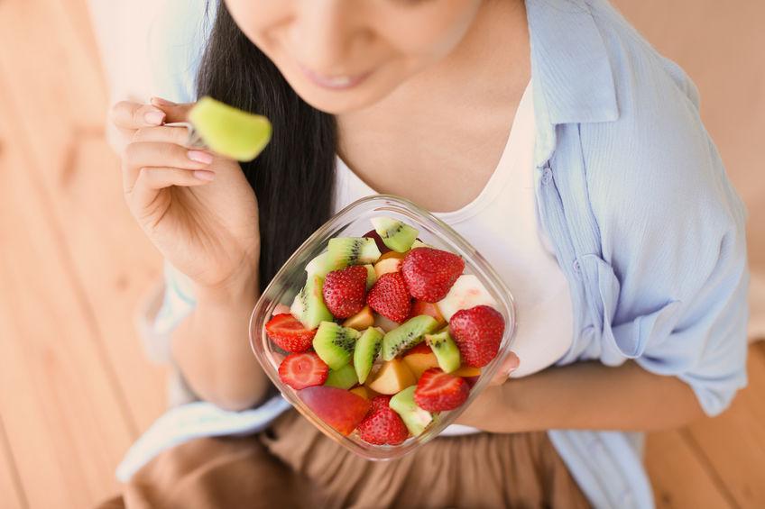 Donna con macedonia di frutta