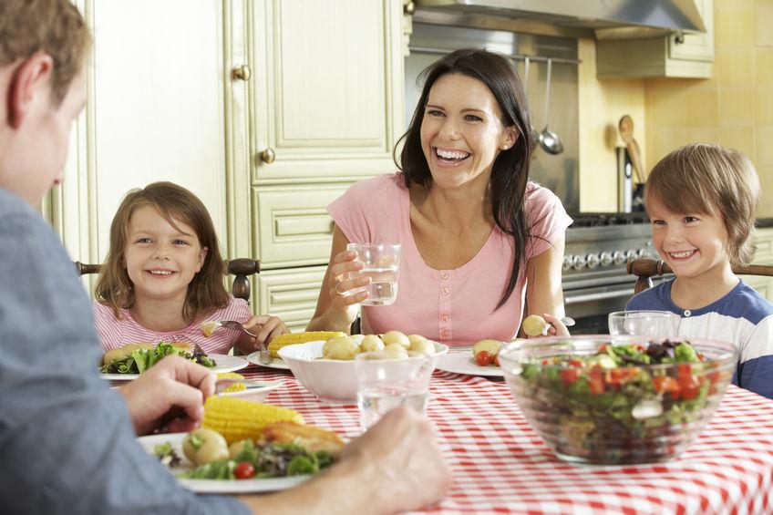 Famiglia sorridente a tavola