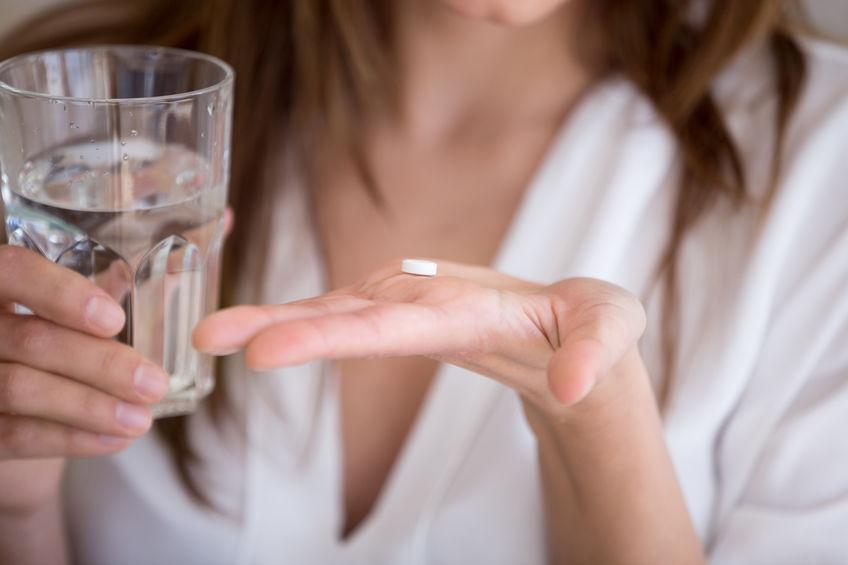 Pillola in mano con un bicchiere di acqua