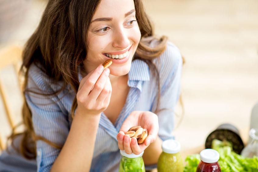 Donna che mangia noci brasiliane