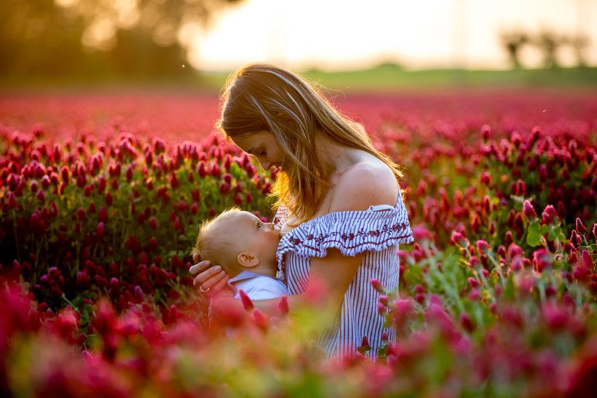 Donna che allatta in un campo di fiori