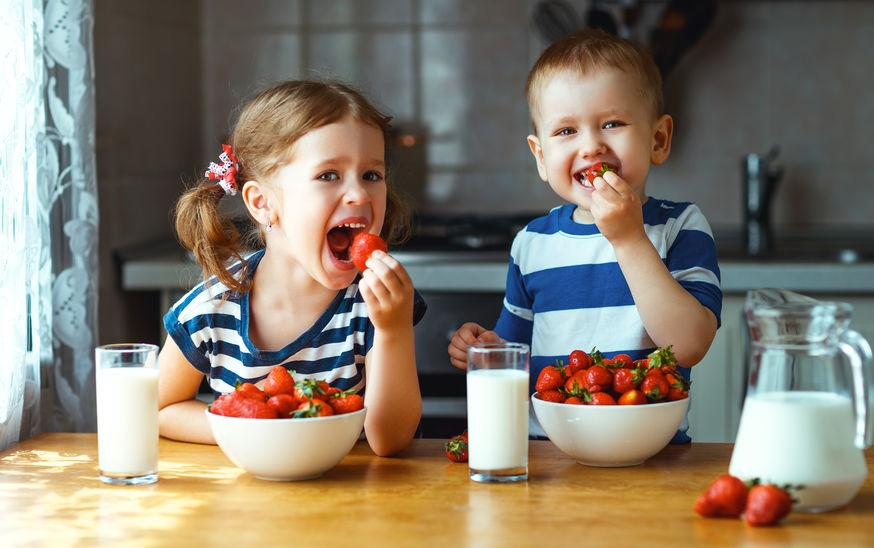 Bambini che mangiano fragole e bevono latte
